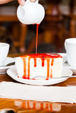 Dessert - pour red syrup on cheese cake. On white dish, on wood table in coffee shop, side view Royalty Free Stock Image