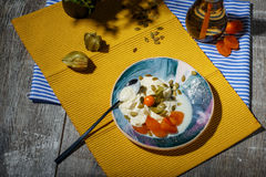 A dessert with pumpkin seeds, physalis and dried apricots on a colorful background. A plant and a drink near a stock photography