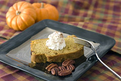 Dessert - Quick Bread, Pumpkin. Plated quick pumpkin bread with a dollop of whipped cream, spiced with nutmeg.  Pecans in the foreground of the plate and mini Stock Photo