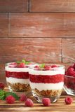 Dessert with raspberries. And granola in glasses brown wooden table Royalty Free Stock Photography