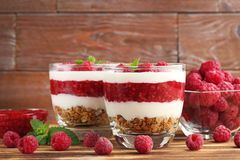 Dessert with raspberries. And granola in glasses on brown wooden table Royalty Free Stock Images