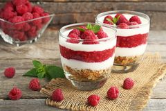 Dessert with raspberries. And granola in glasses on grey wooden table Stock Image
