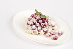 Dessert with raspberries in a white plate. Tasty dessert in a white plate on a white table Stock Images