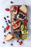 Dessert sandwiches with berries. Variety of dessert sandwiches with berries and cream cheese and chocolate swirl. Red currant, blueberries, sliced kiwi, figs on Stock Photo