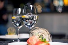 Dessert saporito con i bicchieri d'acqua sulla tavola in ristorante Fotografia Stock