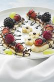 Dessert. From a slice of banana with berries and chocolate topping Stock Images