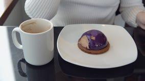 Dessert squisito Una donna in un caffè bevente del caffè con un dolce stock footage