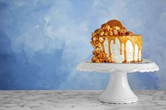 Dessert stand with delicious caramel cake on table. Against color background stock image