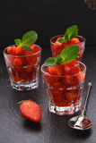 Dessert of strawberries decorated with mint leaves Stock Photos