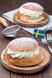 Dessert suédois traditionnel Semla ou petit pain Shrove, avec la pâte d'amande et le remplissage fouetté de crème, verticaux photo libre de droits