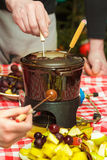 Dessert sweet chocolate fondue party with pieces of apples, pears, pineapples and grapes Royalty Free Stock Image