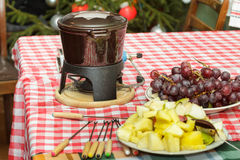 Dessert sweet chocolate fondue party with slices of apples, pears, pineapples and grapes Stock Photos