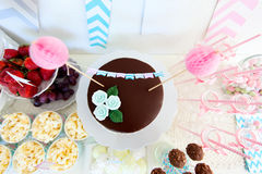 Dessert table. Berries, popcorn, canapes, candies and a chocolate cake on a dessert table at party Royalty Free Stock Photography
