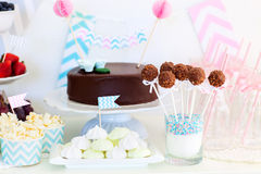 Dessert table. Berries, popcorn, canapes, candies and a chocolate cake on a dessert table at party Royalty Free Stock Image