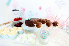 Dessert table. Berries, popcorn, canapes, candies, chocolate cake pops and a cake on a dessert table at party Royalty Free Stock Photography