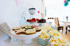 Dessert table. Berries, popcorn, canapes, candies, chocolate cake pops and a cake on a dessert table at party Royalty Free Stock Images