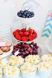 Dessert table. Berries, popcorn and canapes on a dessert table at party Royalty Free Stock Images