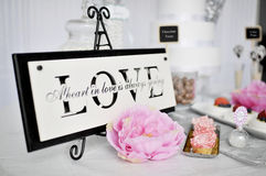 Dessert table. Love sign on a standrnDessert table Royalty Free Stock Image