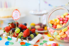 Dessert table at party. Cake, candies, marshmallows, cakepops, fruits and other sweets on dessert table at kids birthday party Royalty Free Stock Image