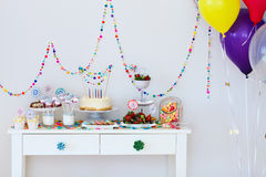 Dessert table at party. Cake, candies, marshmallows, cakepops, fruits and other sweets on dessert table at kids birthday party Stock Image