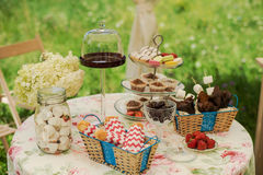 Dessert table for a party. Chocolate cake, cupcakes, sweetness, macaroons, marshmallows, zephyr and flowers. Chocolate cake, cupcakes, sweetness, macaroons Stock Images