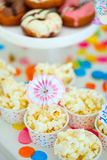 Dessert table at party. Colorful decoration of kids birthday party table with popcorn and sweets Royalty Free Stock Images