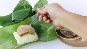 Dessert thaïlandais : Riz collant et crème anglaise cuite à la vapeur avec enveloppé dans la feuille de banane sur le fond blanc banque de vidéos
