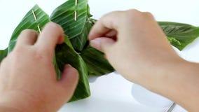 Dessert thaïlandais : Riz visqueux avec l'écrimage sec de poissons avec enveloppé dans la feuille de banane sur le fond blanc banque de vidéos