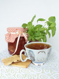 Dessert time. Jam bank, a cup of tea and biscuits on a lacy napkin Stock Photos