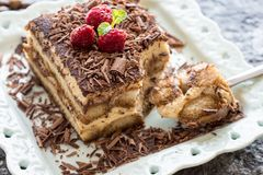 Dessert Tiramisu Cake with Grated Chocolate, Raspberry and Mint Stock Photo