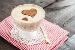 Dessert tiramisu decorated with hearts on a red napkin and a gol Royalty Free Stock Images