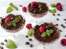 Dessert Tiramisu in glass goblet with mint coffee beans and fresh raspberries on white wooden table.  Royalty Free Stock Image