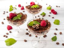 Dessert Tiramisu in glass goblet with mint coffee beans and fresh raspberries on white wooden table.  Royalty Free Stock Photo