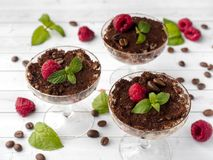 Dessert Tiramisu in glass goblet with mint coffee beans and fresh raspberries on white wooden table.  Stock Photo