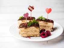 Dessert Tiramisu with mint and fresh raspberries on white wooden table. Red hearts Valentine`s Day.  Stock Images