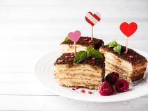 Dessert Tiramisu with mint and fresh raspberries on white wooden table. Red hearts Valentine`s Day Cjpy space. Dessert Tiramisu with mint and fresh raspberries Stock Images