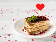 Dessert Tiramisu with mint and fresh raspberries on white wooden table. Red hearts Valentine`s Day Cjpy space. Dessert Tiramisu with mint and fresh raspberries Royalty Free Stock Images