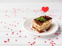 Dessert Tiramisu with mint and fresh raspberries on white wooden table. Red hearts Valentine`s Day Cjpy space. Dessert Tiramisu with mint and fresh raspberries Royalty Free Stock Photos