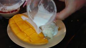 Dessert traditionnel tha? Mangue douce avec du lait de riz et de noix de coco banque de vidéos