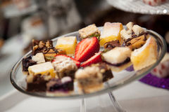 Dessert tray. A glass tray with various sweets garnished with strawberries for dessert Stock Photography