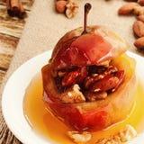Dessert van gebakken die appelen met noten worden en met slijpsteen worden gemotregend gevuld die stock fotografie