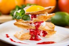 Dessert van vlokkig gebakje met slagroom en aardbeisaus Stock Foto