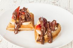 Dessert waffles with banana, strawberry, chocolate. Dessert waffles with banana, strawberry, chocolate on a white plate Stock Images