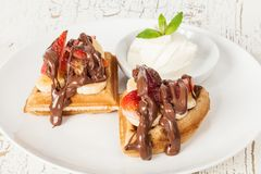 Dessert waffles with banana, strawberry, chocolate and ice cream. On a white plate Stock Photos