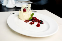 Dessert of white chocolate and wild berries. On a table Royalty Free Stock Photos