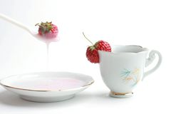 Dessert with yogurt and strawberry. Breakfast. Cup of tea, yogurt and strawberry in the spoon on white Royalty Free Stock Photo