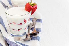 Dessert yogurt and strawberry layers in a glass on a blue stripe Royalty Free Stock Photo