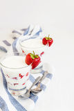 Dessert yogurt and strawberry layers in a glass on a blue stripe Stock Photography