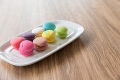 Dessertmakaron in een schotel met een houten achtergrond wordt geplaatst die Stock Foto