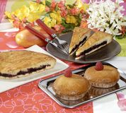 Desserts. Selection of fruit tarts and pastries, slices cut out, platter and forks, flowers in background Royalty Free Stock Photos